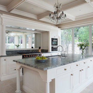 This is an example of a large traditional single-wall eat-in kitchen in Dublin with a drop-in sink, shaker cabinets, white cabinets, quartzite benchtops, mirror splashback, black appliances, ceramic floors, with island, grey floor and green benchtop.