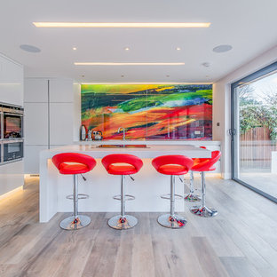 Inspiration for a medium sized contemporary kitchen in London with flat-panel cabinets, white cabinets, quartz worktops, multi-coloured splashback, glass sheet splashback, stainless steel appliances and an island.