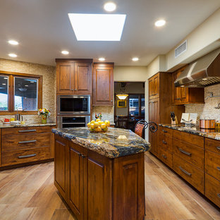 Large country u-shaped kitchen pantry in Phoenix with flat-panel cabinets, distressed cabinets, solid surface benchtops, beige splashback, travertine splashback, stainless steel appliances, porcelain floors, with island, brown floor, black benchtop and an integrated sink.