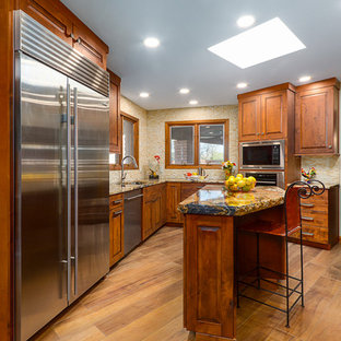Design ideas for a large country u-shaped kitchen pantry in Phoenix with an integrated sink, flat-panel cabinets, distressed cabinets, solid surface benchtops, beige splashback, travertine splashback, stainless steel appliances, porcelain floors, with island, brown floor and black benchtop.