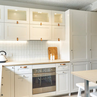 Inspiration for a small beach style l-shaped kitchen pantry in Melbourne with a farmhouse sink, shaker cabinets, white cabinets, laminate benchtops, white splashback, ceramic splashback, stainless steel appliances, vinyl floors, a peninsula, grey floor and beige benchtop.