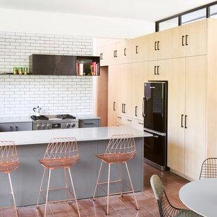 На фото: угловая кухня-гостиная в современном стиле с врезной раковиной, плоскими фасадами, светлыми деревянными фасадами, белым фартуком, фартуком из плитки кабанчик, техникой из нержавеющей стали, полом из терракотовой плитки, полуостровом и розовым полом с