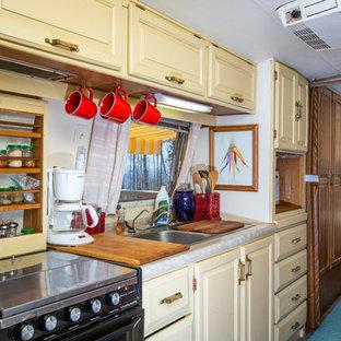 Einzeilige, Kleine Stilmix Küche mit Vorratsschrank, Doppelwaschbecken, profilierten Schrankfronten, beigen Schränken, Laminat-Arbeitsplatte, Küchenrückwand in Beige, Elektrogeräten mit Frontblende, Teppichboden und Kücheninsel in Sonstige