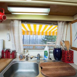 他の地域の小さいエクレクティックスタイルのおしゃれなキッチン (ダブルシンク、レイズドパネル扉のキャビネット、ベージュのキャビネット、ラミネートカウンター、ベージュキッチンパネル、パネルと同色の調理設備、カーペット敷き、アイランドなし) の写真