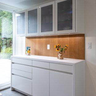トロントのおしゃれなキッチン (フラットパネル扉のキャビネット、白いキャビネット、オレンジのキッチンパネル、木材のキッチンパネル) の写真