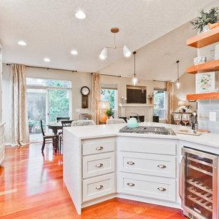 ポートランドの中サイズのトランジショナルスタイルのおしゃれなキッチン (アンダーカウンターシンク、シェーカースタイル扉のキャビネット、グレーのキャビネット、クオーツストーンカウンター、青いキッチンパネル、セラミックタイルのキッチンパネル、シルバーの調理設備の、無垢フローリング、赤い床、白いキッチンカウンター) の写真