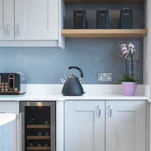 Modelo de cocina comedor en L, moderna, pequeña, con fregadero encastrado, armarios estilo shaker, puertas de armario blancas, encimera de granito, salpicadero azul, salpicadero de azulejos de vidrio, electrodomésticos negros, suelo de piedra caliza, una isla, suelo gris y encimeras blancas