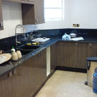 Large modern u-shaped separate kitchen in Other with a double-bowl sink, flat-panel cabinets, dark wood cabinets, granite benchtops, black splashback, stone slab splashback, panelled appliances, travertine floors and with island.