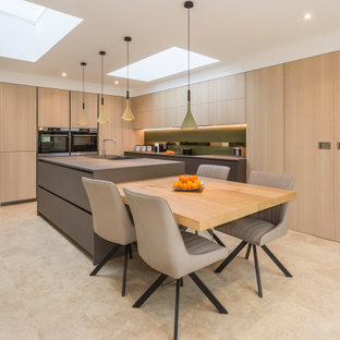 This is an example of a large contemporary l-shaped kitchen in Devon with a built-in sink, flat-panel cabinets, light wood cabinets, integrated appliances, porcelain flooring, an island, beige floors and grey worktops.