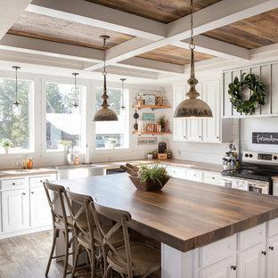 На фото: угловая кухня в стиле кантри с раковиной в стиле кантри, фасадами с выступающей филенкой, белыми фасадами, деревянной столешницей, белым фартуком, техникой из нержавеющей стали, паркетным полом среднего тона и островом с