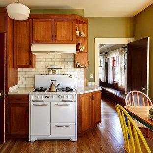 Foto de cocina de estilo americano, de tamaño medio, cerrada, con fregadero bajoencimera, armarios estilo shaker, puertas de armario de madera oscura, encimera de cuarzo compacto, salpicadero blanco, salpicadero de azulejos de cerámica, electrodomésticos blancos y suelo de madera en tonos medios