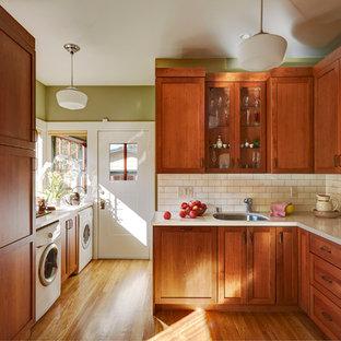 Aménagement d'une cuisine craftsman en L fermée et de taille moyenne avec un évier encastré, un placard à porte shaker, des portes de placard en bois brun, un plan de travail en quartz modifié, une crédence blanche, une crédence en carreau de céramique, un électroménager blanc et un sol en bois brun.
