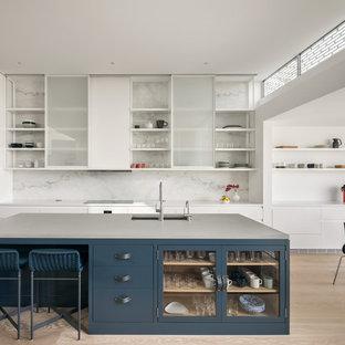 Inredning av ett modernt stort kök, med bänkskiva i betong, vitt stänkskydd, stänkskydd i marmor, ljust trägolv, en köksö, en undermonterad diskho, vita skåp och beiget golv
