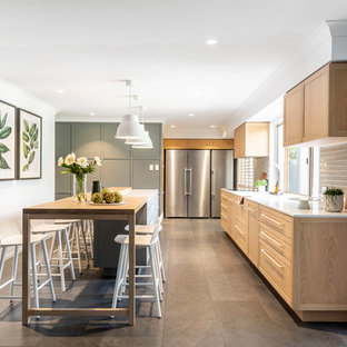 Design ideas for a mid-sized transitional l-shaped kitchen in Brisbane with an undermount sink, shaker cabinets, medium wood cabinets, grey splashback, glass tile splashback, stainless steel appliances, with island, beige floor and white benchtop.