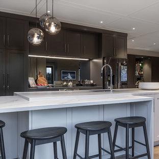 Inspiration för stora klassiska kök och matrum, med vita skåp, spegel som stänkskydd, rostfria vitvaror, mellanmörkt trägolv, en köksö, luckor med infälld panel, kaklad bänkskiva, stänkskydd med metallisk yta, brunt golv och en nedsänkt diskho