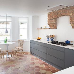 На фото: кухня в современном стиле с обеденным столом, плоскими фасадами, серыми фасадами, техникой из нержавеющей стали и полом из терракотовой плитки с