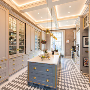 Inspiration for a classic galley enclosed kitchen in Other with a submerged sink, recessed-panel cabinets, grey cabinets, stainless steel appliances, an island, multi-coloured floors and white worktops.