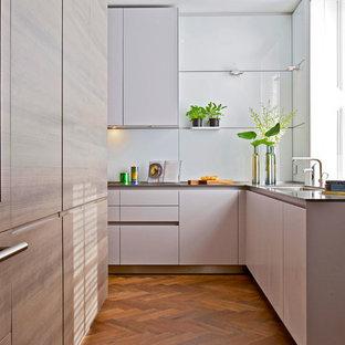 Свежая идея для дизайна: большая угловая, отдельная кухня в современном стиле с врезной раковиной, плоскими фасадами, светлыми деревянными фасадами, белым фартуком, паркетным полом среднего тона, стеклянной столешницей, фартуком из стеклянной плитки и техникой под мебельный фасад без острова - отличное фото интерьера