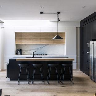 Ispirazione per una cucina moderna di medie dimensioni con ante lisce, paraspruzzi in lastra di pietra, isola, lavello a vasca singola, elettrodomestici in acciaio inossidabile, parquet chiaro e ante nere