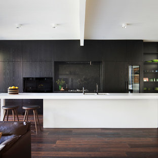 Modern galley open plan kitchen in Melbourne with a double-bowl sink, flat-panel cabinets, black cabinets, black splashback, panelled appliances, dark hardwood floors, with island and brown floor.