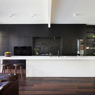 Modelo de cocina de galera, moderna, abierta, con fregadero de doble seno, armarios con paneles lisos, puertas de armario negras, salpicadero negro, electrodomésticos con paneles, suelo de madera oscura, una isla y suelo marrón