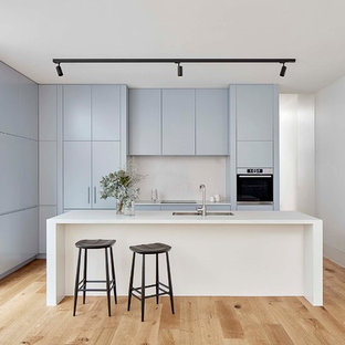 Inspiration for a mid-sized contemporary galley kitchen in Melbourne with a double-bowl sink, blue cabinets, quartz benchtops, white splashback, stone slab splashback, stainless steel appliances, light hardwood floors, with island, white benchtop, flat-panel cabinets and brown floor.