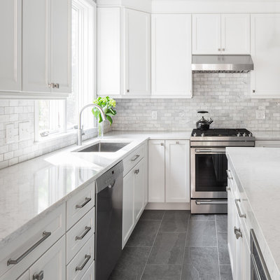 Inspiration for a large transitional slate floor and gray floor open concept kitchen remodel in Boston with an undermount sink, white cabinets, quartzite countertops, white backsplash, marble backsplash, stainless steel appliances, an island and recessed-panel cabinets