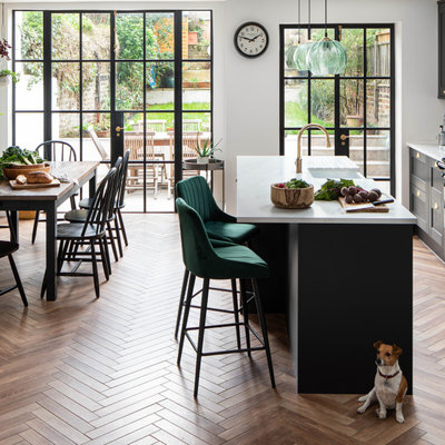 Example of a transitional galley medium tone wood floor and brown floor kitchen design in London with a farmhouse sink, shaker cabinets, black cabinets, an island and white countertops