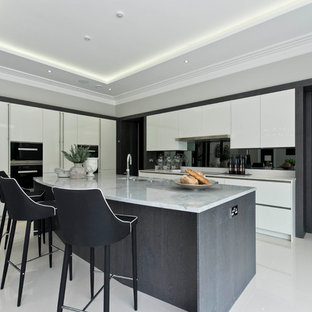 This is an example of a contemporary l-shaped kitchen in Surrey with flat-panel cabinets, white cabinets, black splashback, black appliances, an island and white floors.