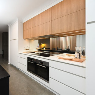 Inspiration for a modern galley eat-in kitchen in Other with a double-bowl sink, medium wood cabinets, limestone benchtops, mirror splashback, stainless steel appliances, cement tiles, with island, grey floor and black benchtop.