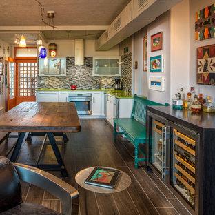 アルバカーキの中サイズのエクレクティックスタイルのおしゃれなキッチン (アンダーカウンターシンク、フラットパネル扉のキャビネット、白いキャビネット、クオーツストーンカウンター、マルチカラーのキッチンパネル、ボーダータイルのキッチンパネル、シルバーの調理設備の、磁器タイルの床、アイランドなし) の写真