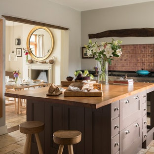 This is an example of a medium sized rural l-shaped open plan kitchen in Other with brown cabinets, wood worktops, an island, beige floors, black worktops, recessed-panel cabinets, metallic splashback, metal splashback and stainless steel appliances.