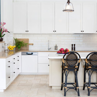 Photo of a mid-sized transitional kitchen in Brisbane with a drop-in sink, shaker cabinets, white cabinets, white splashback, subway tile splashback, panelled appliances, with island, beige floor and beige benchtop.