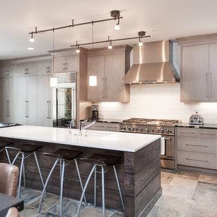 ソルトレイクシティの広いコンテンポラリースタイルのおしゃれなキッチン (アンダーカウンターシンク、フラットパネル扉のキャビネット、淡色木目調キャビネット、白いキッチンパネル、シルバーの調理設備、サブウェイタイルのキッチンパネル、茶色い床、御影石カウンター) の写真