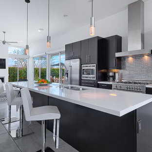 Inspiration for a mid-sized mid-century modern galley concrete floor open concept kitchen remodel in Other with an undermount sink, dark wood cabinets, quartz countertops, metallic backsplash, metal backsplash, stainless steel appliances and an island