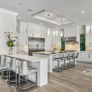 Photo of a contemporary u-shaped eat-in kitchen in Miami with an undermount sink, shaker cabinets, white cabinets, marble benchtops, beige splashback, marble splashback, stainless steel appliances, medium hardwood floors, with island, brown floor, white benchtop and coffered.