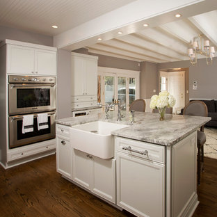 Enclosed kitchen - mid-sized traditional u-shaped medium tone wood floor enclosed kitchen idea in DC Metro with a farmhouse sink, recessed-panel cabinets, white cabinets, granite countertops, gray backsplash, stainless steel appliances and an island