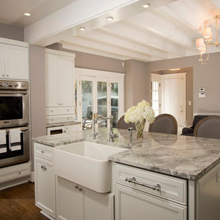 Mid-sized elegant l-shaped dark wood floor open concept kitchen photo in DC Metro with a farmhouse sink, recessed-panel cabinets, white cabinets, granite countertops, gray backsplash, stainless steel appliances and an island