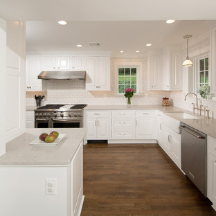 Mid-sized traditional enclosed kitchen remodeling - Inspiration for a mid-sized timeless u-shaped medium tone wood floor and brown floor enclosed kitchen remodel in DC Metro with a farmhouse sink, raised-panel cabinets, white cabinets, quartz countertops, gray backsplash, subway tile backsplash, stainless steel appliances and no island