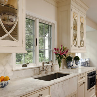 Mid-sized traditional eat-in kitchen remodeling - Mid-sized elegant u-shaped medium tone wood floor eat-in kitchen photo in DC Metro with beaded inset cabinets, white cabinets, marble countertops, white backsplash, stone slab backsplash, stainless steel appliances, an island and an undermount sink