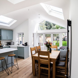 This is an example of a mid-sized contemporary l-shaped open plan kitchen in Surrey with a farmhouse sink, shaker cabinets, blue cabinets, limestone benchtops, grey splashback, glass sheet splashback, stainless steel appliances, laminate floors, with island, brown floor and white benchtop.