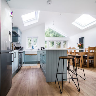 Design ideas for a mid-sized contemporary l-shaped open plan kitchen in Surrey with a farmhouse sink, shaker cabinets, blue cabinets, limestone benchtops, grey splashback, glass sheet splashback, stainless steel appliances, laminate floors, with island, brown floor and white benchtop.