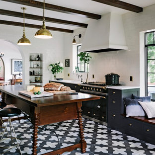 This is an example of a mediterranean kitchen in Portland with shaker cabinets, black cabinets, white splashback, metro tiled splashback, black appliances, an island and ceramic flooring.