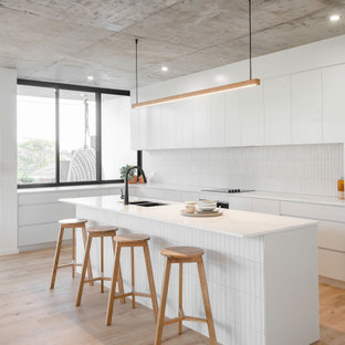 Design ideas for a large contemporary l-shaped kitchen in Sydney with an undermount sink, flat-panel cabinets, white cabinets, white splashback, porcelain splashback, panelled appliances, with island, beige floor and white benchtop.