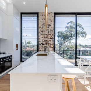 Design ideas for a large contemporary galley eat-in kitchen in Sydney with a double-bowl sink, flat-panel cabinets, white cabinets, white splashback, porcelain splashback, panelled appliances, light hardwood floors, with island, beige floor and white benchtop.