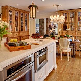 ニューヨークのおしゃれなダイニングキッチン (ガラス扉のキャビネット、シルバーの調理設備、エプロンフロントシンク、白いキャビネット、大理石カウンター) の写真