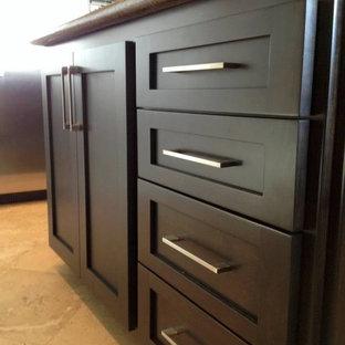 Foto di una cucina minimal di medie dimensioni con ante in stile shaker, ante in legno bruno, top in granito, paraspruzzi verde, paraspruzzi con lastra di vetro, elettrodomestici in acciaio inossidabile, pavimento in travertino e isola