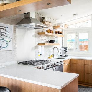 Immagine di una cucina ad U minimalista con lavello sottopiano, ante lisce, ante in legno chiaro, paraspruzzi a effetto metallico, elettrodomestici in acciaio inossidabile e penisola