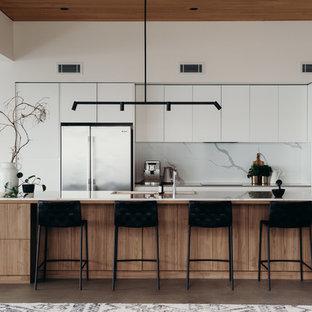 ニューカッスルの大きいコンテンポラリースタイルのおしゃれなキッチン (クオーツストーンカウンター、石スラブのキッチンパネル、コンクリートの床、アンダーカウンターシンク、ガラス扉のキャビネット、白いキャビネット、白いキッチンパネル、シルバーの調理設備の、グレーの床、白いキッチンカウンター) の写真