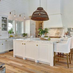Foto di una grande cucina country con ante bianche, parquet chiaro, isola, top in marmo, elettrodomestici bianchi, lavello sottopiano, paraspruzzi grigio, paraspruzzi in lastra di pietra e ante in stile shaker